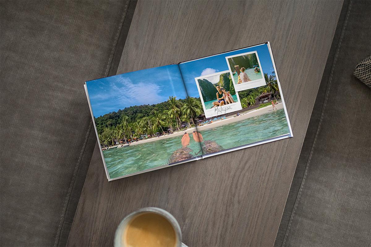 Een open fotoboek op een houten tafelblad. Je ziet een foto die verspreid is over twee pagina's van een vrouw die in de zee drijft met het strand en palmbomen op de achtergrond en twee afbeeldingen in de stijl van instant camera in de rechterbovenhoek.