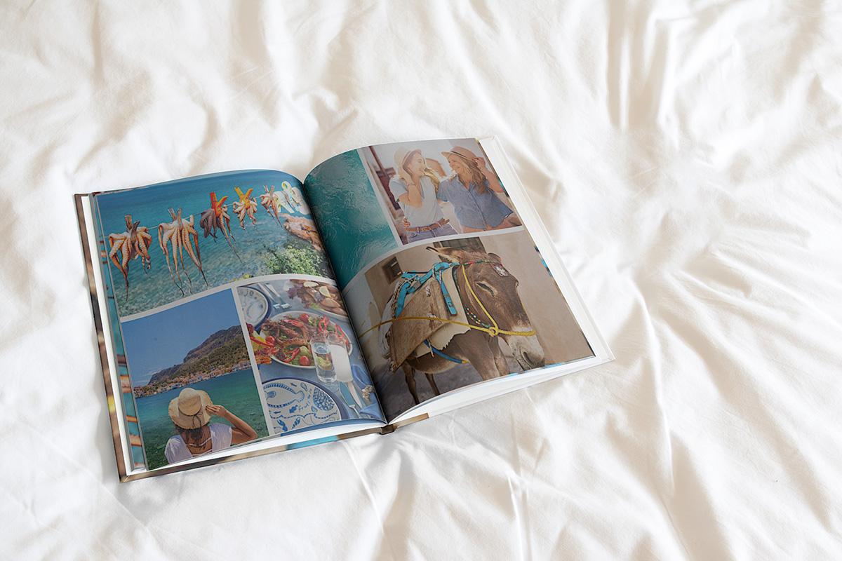 Een fotoboek open op een wit dekbedovertrek. Je ziet op beide pagina's een raster met drie afbeeldingen, elk met een zomerse foto erin.